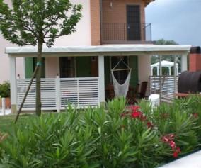 Pergolato in legno di abete lamellare sbiancato con grigliati lineari perimetrali e copertura in bambu' e pvc