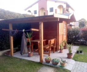 casetta ad incastro con veranda laterale e stendi biancheria incorporato tra le colonne in legno di abete massello