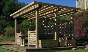 Pergolato con tetto grigliato in legno di abete lamellare con chiusure in grigliato e fioriere